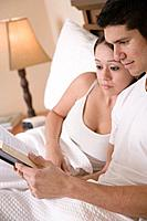 Hispanic couple reading book in bed