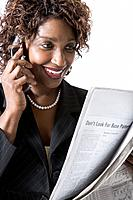 Mixed race businesswoman talking on cell phone and reading newspaper