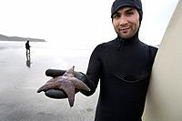 Surfer holding starfish