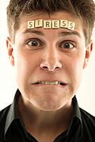 Man with the word ´stressed´ spelled with letter tiles on his head