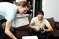 Men playing video games, with pizza boxes