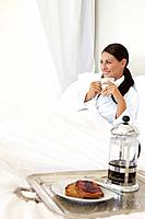 Woman relaxing in bed with breakfast