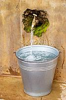 Clean water from old tape in metal bucket, Malawi