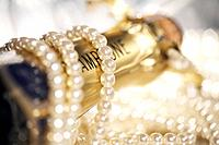Pearls wrapped around champagne bottle