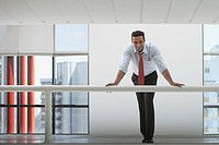 Businessman leaning over railing