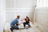 Couple play fighting while painting