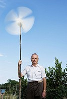 England, Isle of Wight, senior man holding wind turbine in garden, portrait