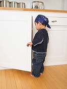 Baby boy 21_24 months looking into kitchen cabinets