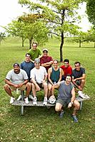 Group men sitting on picnic table with soccer ball, smiling, portrait
