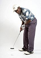 Male golfer putting, studio shot