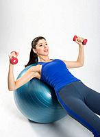 Young woman using dumbbells, lying on exercise ball, studio shot