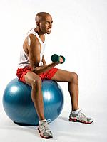 Young man using dumbbell, on exercise ball, studio shot