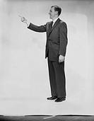 Man in full suit, pointing, side view, studio shot