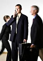Businessman talking on mobile phone, others passing by blurred motion