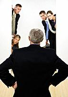 Businessman facing group of business people peeking from behind wall, rear view