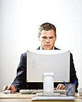 Young businessman working on computer at desk