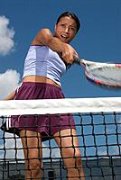 Woman swinging tennis racket behind net, low angle view