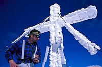 Gipfelkreuz Hochmoelbing, Young man before snow covered summit cross , Hochmoelbing, Totes Gebirge, Upper Austria