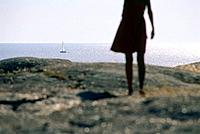 Woman standing on granite rock looking out on sea, Smoegen, Bohuslan, Sweden