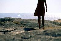 Woman standing on granite rock looking out on sea, Smoegen, Bohuslan, Sweden