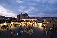 View over busy Platia Ippokratou with Thalassini Gate in background in the evening, Rhodes Town, Rhodes, Greece, Since 1988 part of the UNESCO World H...