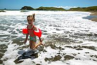 Girl 5y. running in shallow water, campground on the beach, Port Jackson on the northern tip of Coromandel Peninsula, North Island, New Zealand