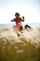 Boy running through meadow of shore grass, Sysne, Gotland, Sweden