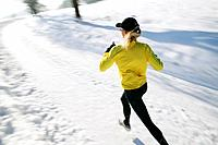 Woman jogging on snowy road, Styria, Austria