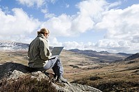 A woman sat on a rock using a laptop
