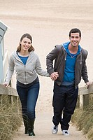 Couple walking stairs from beach