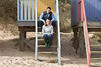 Couple sitting on steps of a beach hut