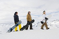 Three people holding snowboards