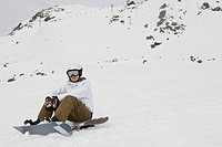 A woman sat on a snowboard