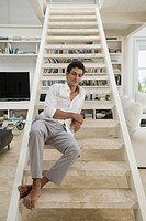 Hispanic man sitting on stairway