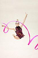 Front view of a teenage girl performing rhythmic gymnastics with ribbon