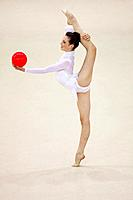 Side view of a young woman performing rhythmic gymnastics with ball