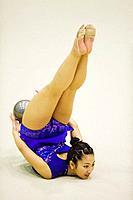Young woman performing rhythmic gymnastics with ball