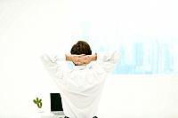 Man stretching with hands behind his head, laptop and cactus on desk, rear view