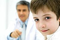 Boy smiling at camera, doctor holding stethoscope in the background