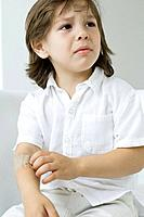 Little boy picking at adhesive bandage on his arm, frowning