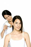 Hair stylist blow drying a woman's hair