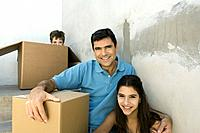 Family sitting on stairwell with cardboard boxes, boy hiding (thumbnail)