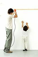 Man drilling into wall, his son reaching up, trying to help