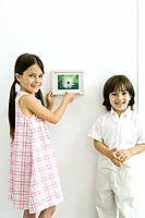 Girl standing beside younger brother, hanging framed picture, both smiling at camera