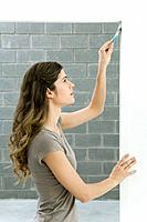 Woman painting doorframe, side view