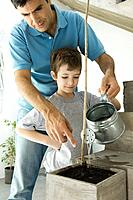 Father and son watering plant together