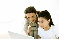 Girl using laptop, young woman looking over her shoulder with interest