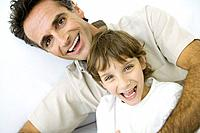 Father with arm wrapped around son, both smiling at camera, portrait