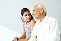 Teenage girl looking at grandfather, man looking away, both smiling