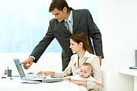 Professional woman in office, holding baby on lap, looking at laptop with male colleague